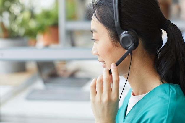 Widok z tyłu azjatyckiego młodego operatora w słuchawkach rozmawiającego z klientem, ona pracuje w obsłudze klienta