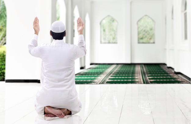 Widok z tyłu azjatyckiego muzułmańskiego mężczyzny siedzącego z podniesionymi rękami i modląc się na meczecie