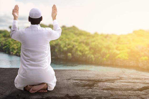 Widok z tyłu azjatyckiego muzułmańskiego mężczyzny siedzącego z podniesionymi rękami i modląc się na świeżym powietrzu