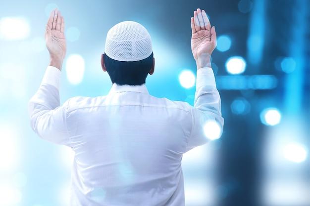 Widok z tyłu azjatyckiego muzułmańskiego mężczyzny stojącego z podniesionymi rękami i modlącego się z niewyraźnymi światłami
