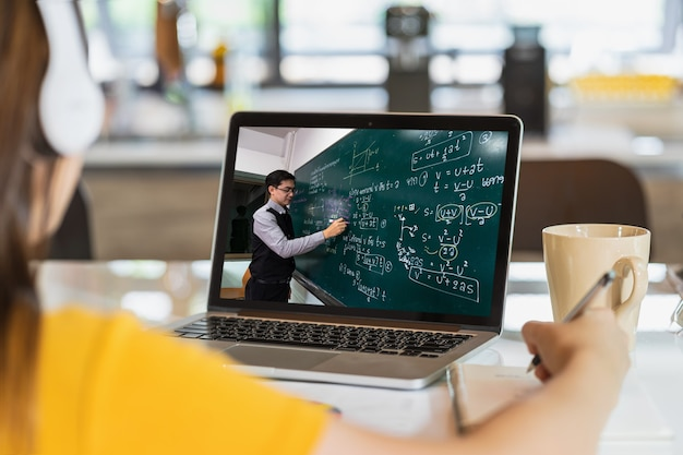 Widok z tyłu azjatyckiego ucznia uczącego się z nauczycielem nad formułą fizyki w języku tajskim