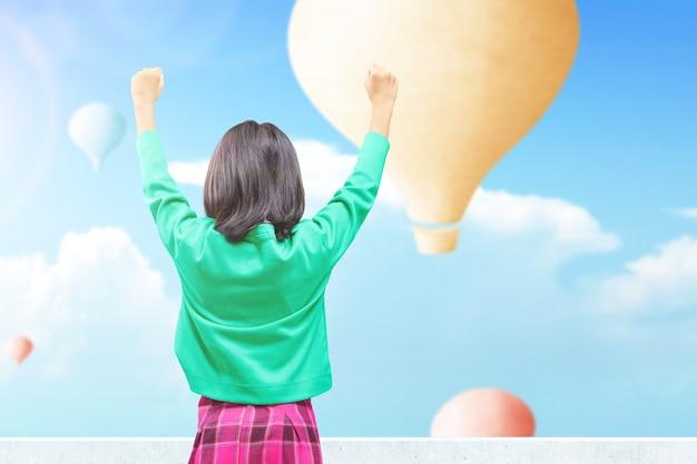 Widok z tyłu azjatyckiej małej dziewczynki patrzącej na kolorowy balon latający na tle błękitnego nieba