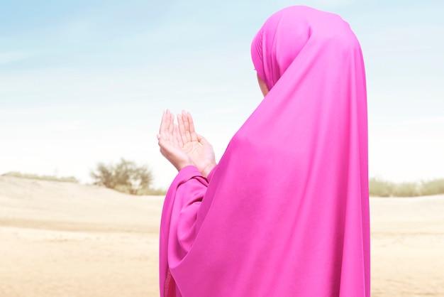 Widok z tyłu azjatyckiej muzułmanki w welonie, stojącej z podniesionymi rękami i modlącej się na wydmie