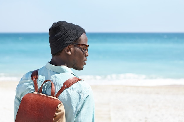 Widok z tyłu beztroskiego młodego ciemnoskórego podróżnika ze skórzanym plecakiem cieszącym się pięknym lazurowym krajobrazem podczas wakacji nad morzem, kontemplując niesamowity widok w słoneczny dzień