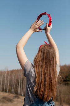 Widok z tyłu beztroskiej kobiety bawiące się tamburyn w przyrodzie