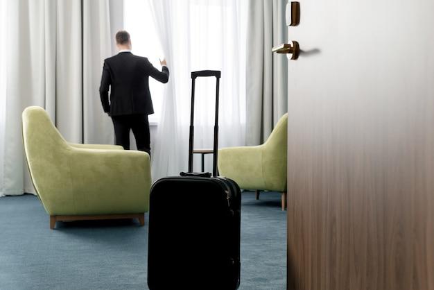 Widok z tyłu biznesmen na sobie ciemny garnitur stojący w pokoju hotelowym, patrząc w okno