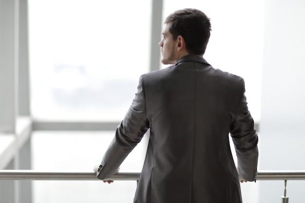 Widok z tyłu. biznesmen w casual stałego i myślenia w pobliżu okna biura.