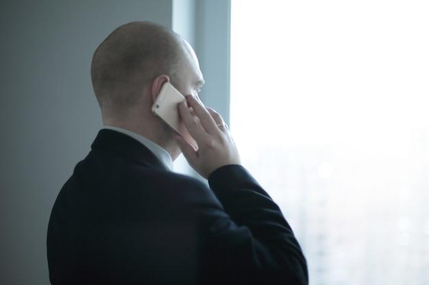 Widok z tyłu .biznesmen ze smartfonem wyglądającym przez okno biura. zdjęcie z miejscem na kopię