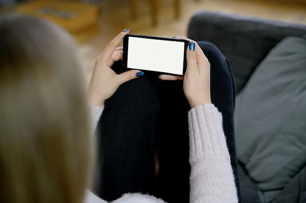 Widok z tyłu bliska kobiety ręki trzymającej i za pomocą inteligentnego telefonu z białym pustym pustym ekranem, siedząc na łóżku w domu. wysokiej jakości zdjęcie