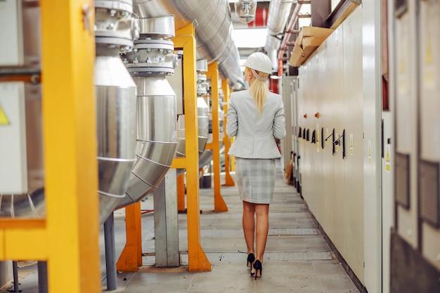 Widok z tyłu blond bizneswoman w garniturze, z maską ochronną, z hełmem na głowie chodzenie przez ciepłownię.