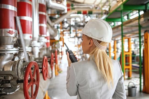 Widok z tyłu blond kobiecej przełożonej w kasku w garniturze stojącej w ciepłowni i rozmawiającej przez wakie talkie ze swoim pracownikiem.