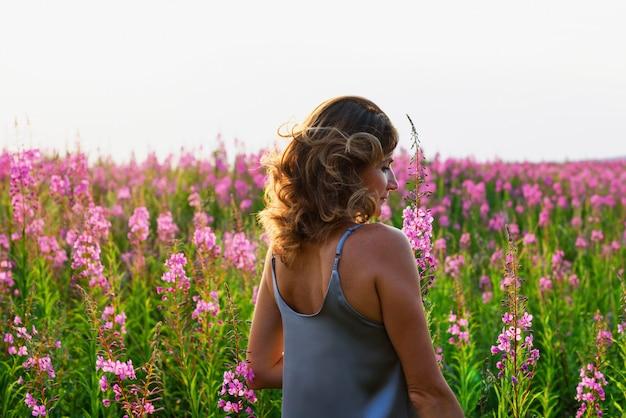 Widok z tyłu blond kobieta na łące fireweed