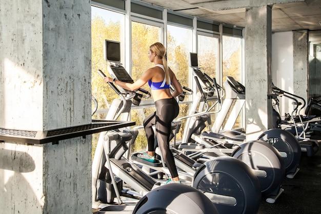 Widok z tyłu blondynki kobiety w fitness clubie na rowerze stacjonarnym