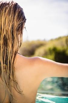 Widok z tyłu blondynki w basenie z rozpostartymi ramionami