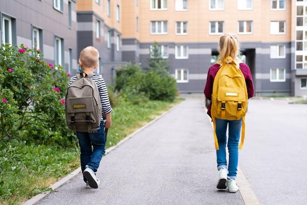 Widok z tyłu brat i siostra idą do szkoły po zakończeniu pandemii. dzieci noszące maskę i plecaki chronią przed koronawirusem na powrót do szkoły.