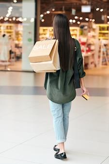 Widok z tyłu brunetki kobiety w swobodnym stroju, niosąc papierowe torby na ramieniu podczas zakupów z kartą kredytową