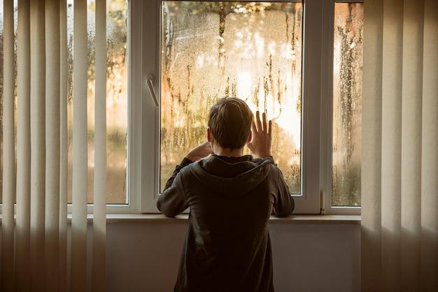 Widok z tyłu chłopiec stojący obok okien