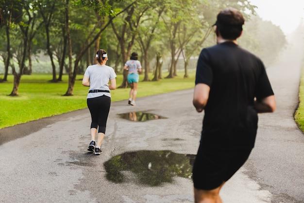 Widok z tyłu ćwiczeń biegaczy w parku wcześnie rano.