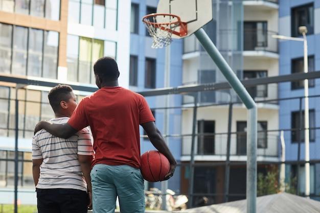 Widok z tyłu czarnego ojca w pomarańczowej koszulce obejmującego ramię syna, gdy stoją przed obręczą do koszykówki