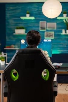 Widok z tyłu czarnej kobiety, grając w kosmiczną strzelankę online. konkurencyjna kobieta gracza cybernetycznego podczas turnieju gier wideo używa profesjonalnego joysticka.