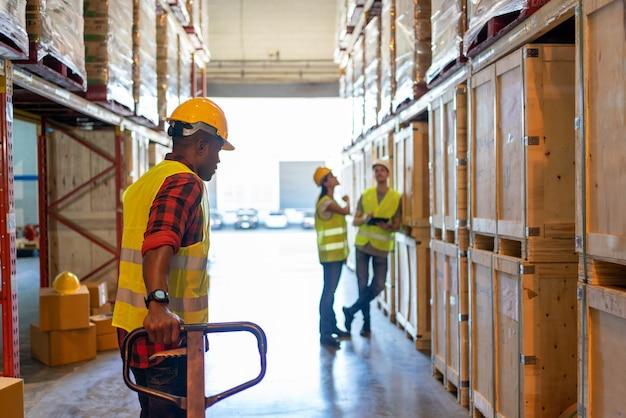 Widok z tyłu czarny męski zespół pracowników pracujących w magazynie fabrycznym. czarny człowiek pracownik ciągnąc wózek paletowy kryty budynku w tle półki z towarami. koncepcja branży logistycznej.