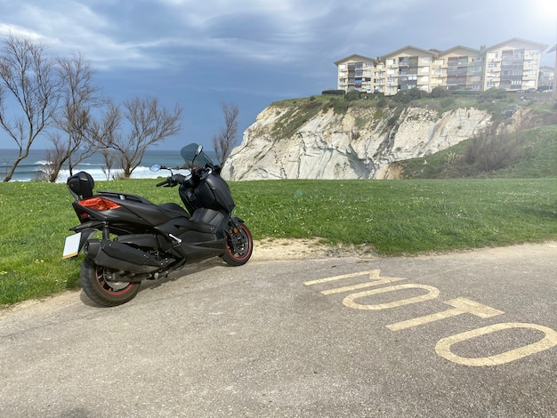 Widok z tyłu czarny skuter zaparkowany przed morzem. jest na parkingu dla motocykli. zielona trawa i urwisko z domami z tyłu. pochmurne niebo