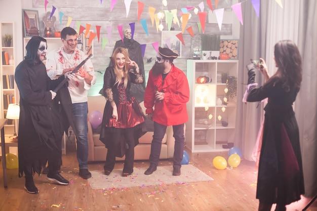 Widok z tyłu czarownica robienia zdjęć ponurego żniwiarza i jego przyjaciół na imprezie z okazji halloween.