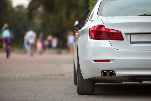 Widok z tyłu części białego samochodu zaparkowanego na chodniku strefy dla pieszych
