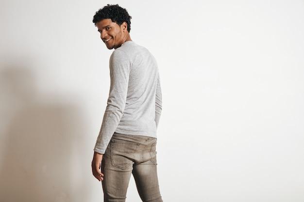 Widok z tyłu człowieka latino patrząc z radosnym uśmiechem, odwracając się, na białym tle na biały, ubrany w puste szare ubrania