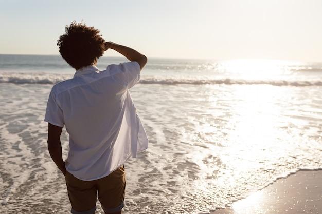 Widok z tyłu człowieka, patrząc na morze na plaży