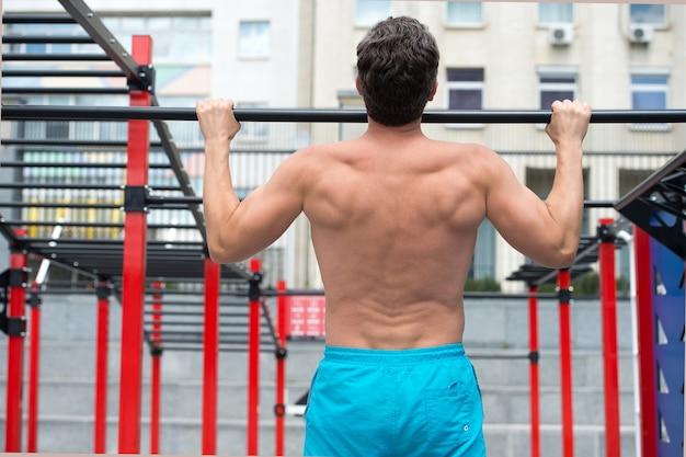 Widok z tyłu człowieka robi podciąganie w koncepcji siłowni ćwiczeń sportowych w siłowni fitness male