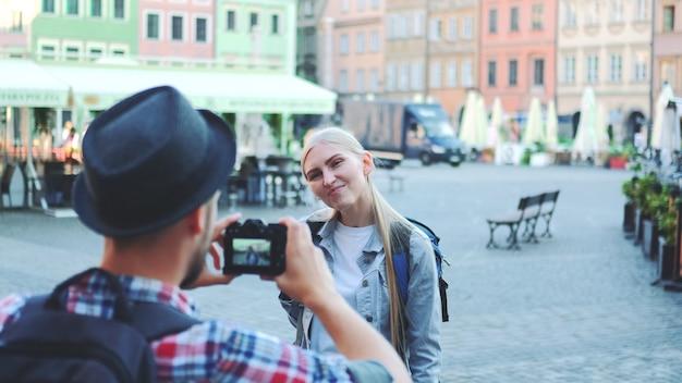 Widok z tyłu człowieka robiącego zdjęcia turystki na rynku miasta