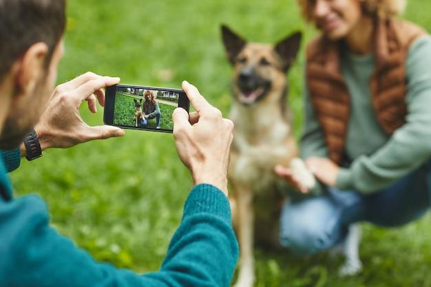 Widok z tyłu człowieka robienie zdjęć na swoim telefonie komórkowym swojej dziewczyny i psa w parku