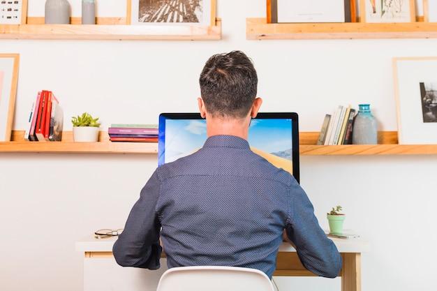 Widok z tyłu człowieka siedzącego na krześle przy użyciu komputera w biurze