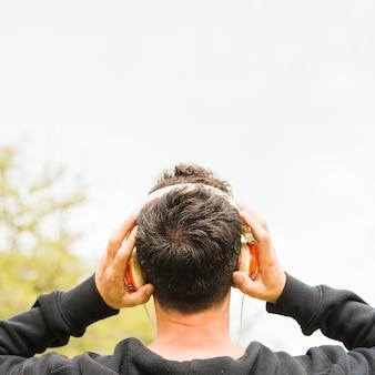 Widok z tyłu człowieka słuchania muzyki na słuchawkach w plenerze
