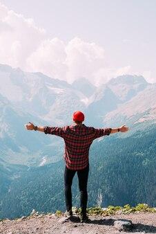 Widok z tyłu człowieka stojącego na tle gór z rozpostartymi ramionami. mężczyzna w górach podnosi ręce. człowiek na tle gór. podróż w góry
