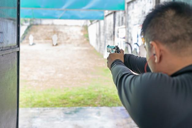 Widok z tyłu człowieka strzelanie z pistoletu na cel w strzelnicy.