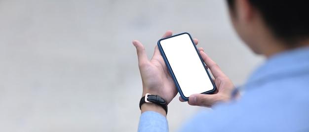 Widok z tyłu człowieka trzymając się za ręce telefon komórkowy z pustym ekranem dla wiadomości tekstowej lub treści informacyjnej.