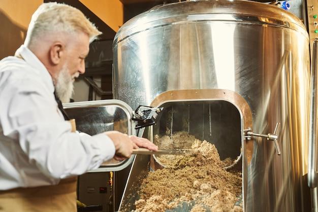 Widok z tyłu człowieka trzymającego łopatę i badającego jakość przemiału w browarze. profesjonalny człowiek w białej koszuli i fartuchu kontrolujący proces produkcji piwa. pojęcie słodu.