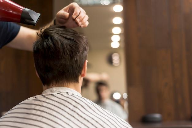 Widok z tyłu człowieka w zakładzie fryzjerskim
