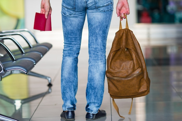Widok z tyłu człowieka z paszportami i plecak w ręce na lotnisku
