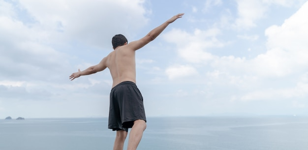 Widok z tyłu człowieka z zachwytem rozłożył ręce na ocean i niebo.