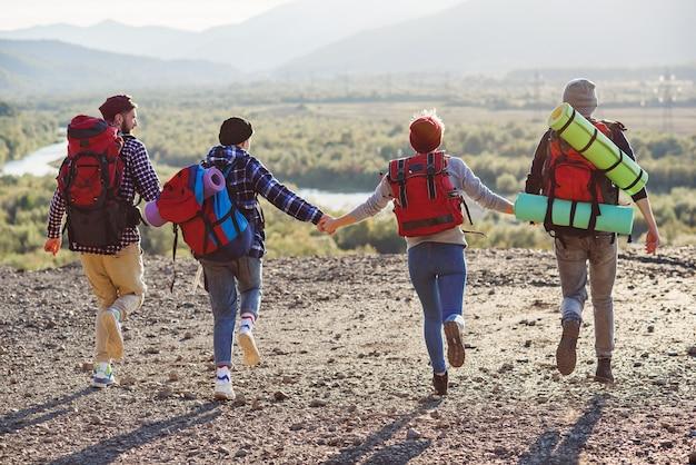 Widok z tyłu czterech przyjaciół hipster z plecakiem podróży trzymając się za ręce