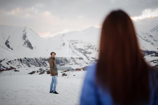 Widok z tyłu długowłosa kobieta patrząc na swojego chłopaka w górach