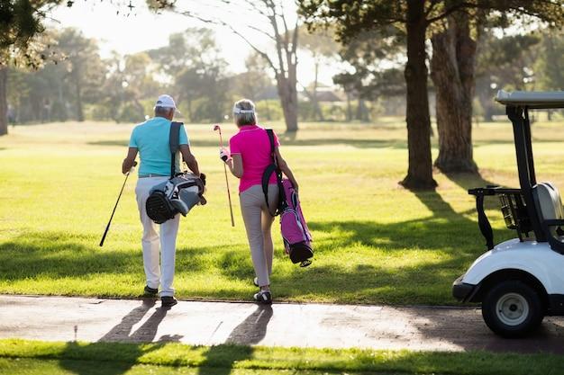 Widok z tyłu dojrzałej pary golfistów