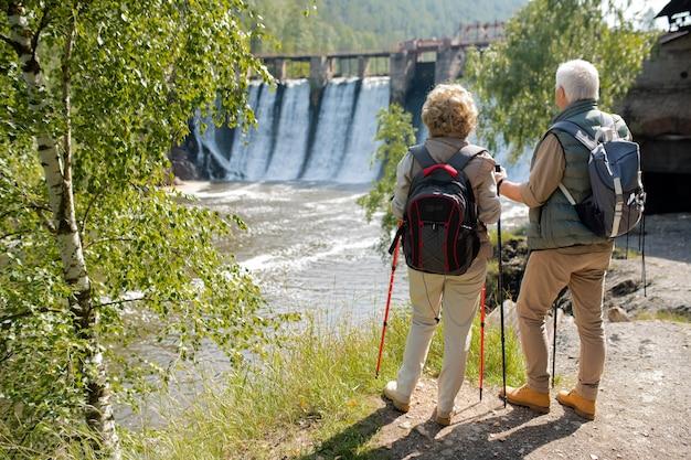 Widok z tyłu dojrzałej pary z plecakami stojąc na brzegu rzeki, patrząc na wodospady przez most