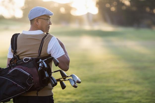 Widok z tyłu dojrzały mężczyzna niesie torbę golfową