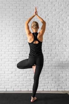 Widok z tyłu dopasowanie kobiety stojącej na jednej nodze