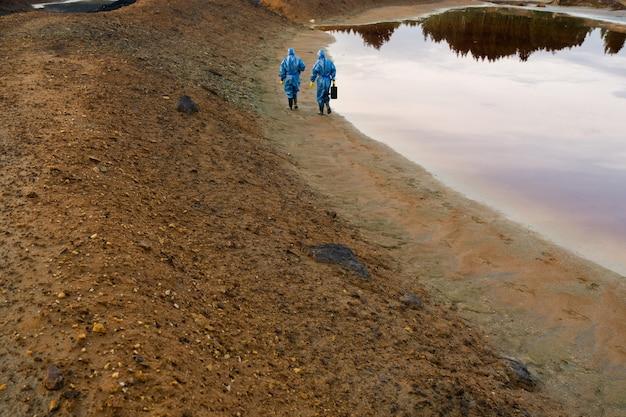 Widok z tyłu dwóch badaczy lub ekologów poruszających się wzdłuż rzeki z brudną wodą i glebą podczas badania terenu