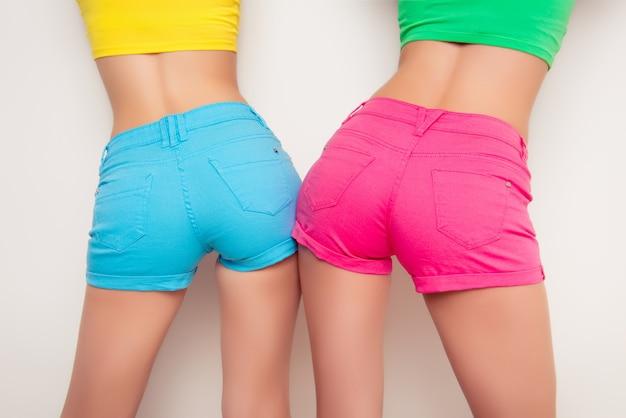 Widok z tyłu dwóch dziewczyn pokazujących ich tyłek